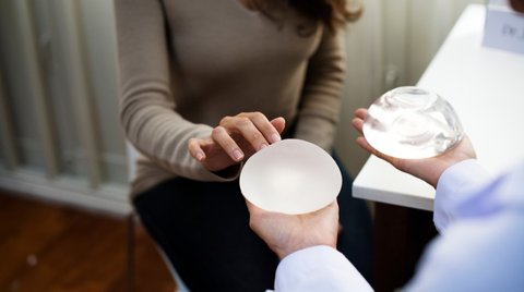 surgeon shows textured and smooth breast implants